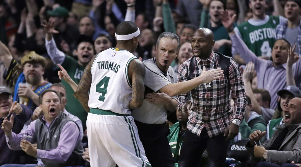 Fans cheer after a 3-pointer by Boston Celtics guard Isaiah Thomas (4), as referee Mike Callahan cuts in front of retired boxer Floyd Mayweather Jr., in plaid shirt, during the second half of the Celtics' NBA basketball game against the Washington Wizards in Boston, Wednesday, Jan. 11, 2017. The Celtics defeated the Wizards 117-108. (AP Photo/Charles Krupa)